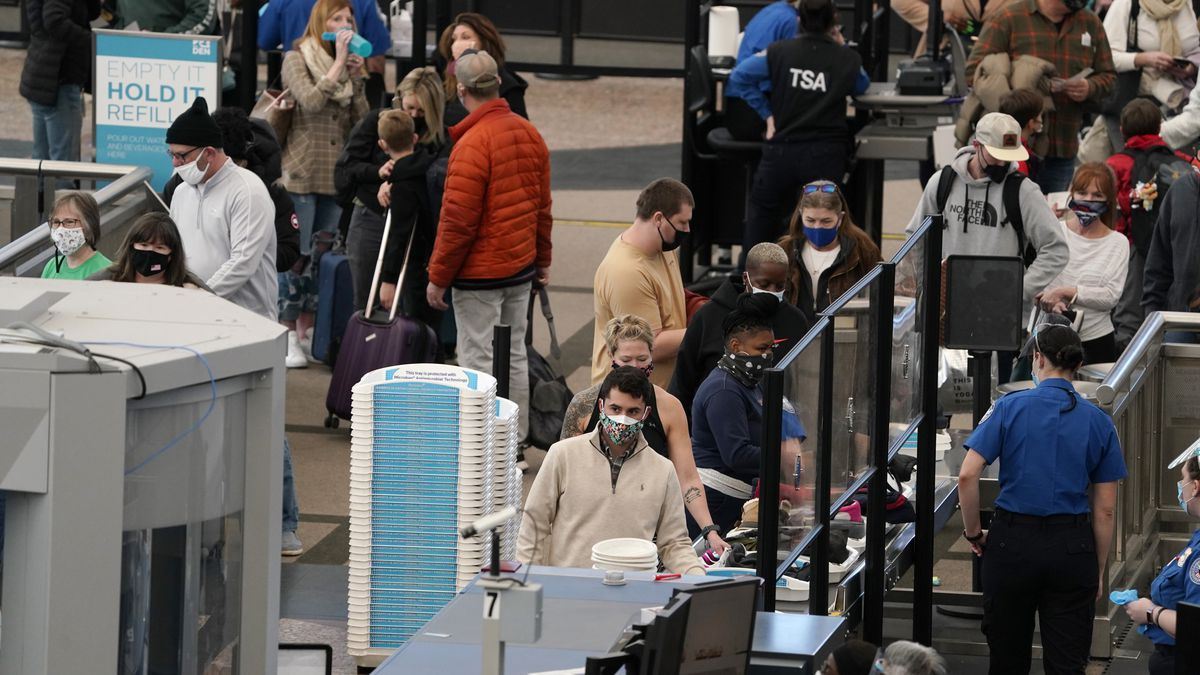 FILE - In this Thursday, Feb. 18, 2021, file photo, travelers wear face coverings as they queue...
