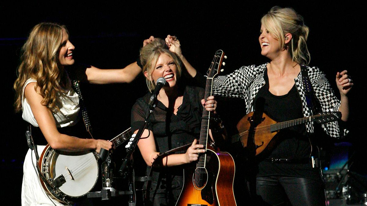 FILE - In this Oct. 18, 2007 file photo, Emily Robison, left, and Martie Maguire, right, adjust Natalie Maines' hair as the Dixie Chicks perform at the new Nokia Theatre in Los Angeles. The Grammy-winning country group have dropped the word dixie from their name and are now going by The Chicks. The move follows a decision by country group Lady Antebellum to change to Lady A after acknowledging the word's association to slavery.(AP Photo/Gus Ruelas, File)