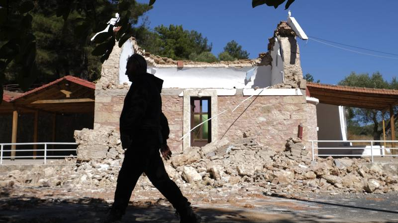 A resident passes next to a damaged Greek Orthodox chapel after a strong earthquake in...