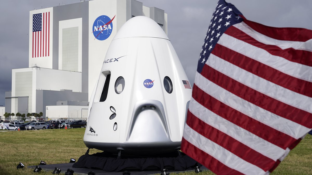 A mockup of the SpaceX crew capsule is seen on display in front of the Vehicle Assembly...