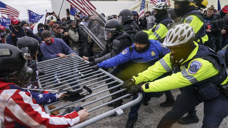 FILE - In this Jan. 6, 2021 file photo, rioters try to break through a police barrier at the...