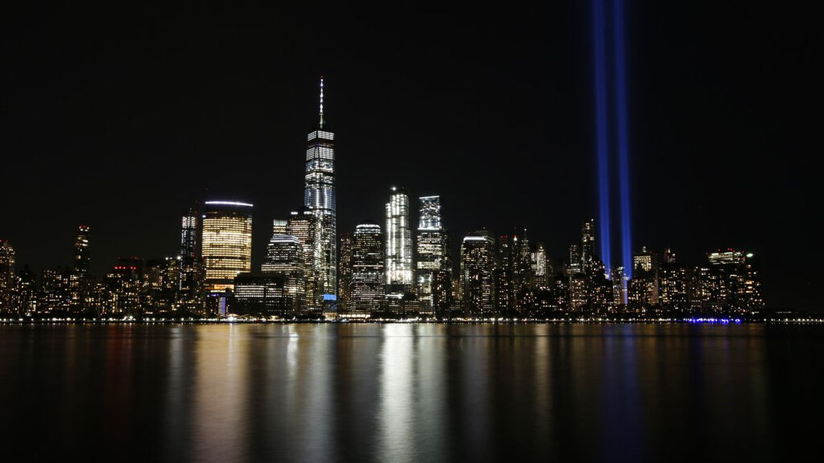In this Sept. 11, 2017, file photo, the Tribute in Light illuminates in the sky above the Lower Manhattan area of New York, as seen from across the Hudson River in Jersey City, N.J. The coronavirus pandemic has reshaped how the U.S. is observing the anniversary of 9/11. The terror attacks' 19th anniversary will be marked Friday, Sept. 11, 2020, by dueling ceremonies at the Sept. 11 memorial plaza and a corner nearby in New York.