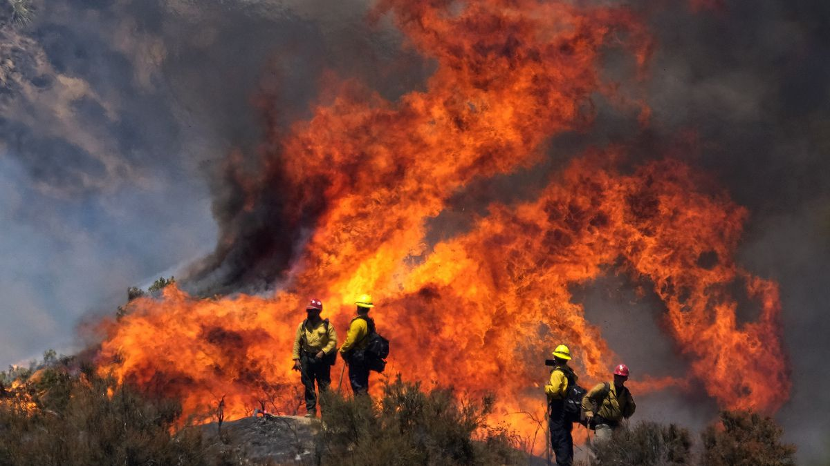 Firefighters watch the Apple Fire in Banning, Calif., Sunday, Aug. 2, 2020.