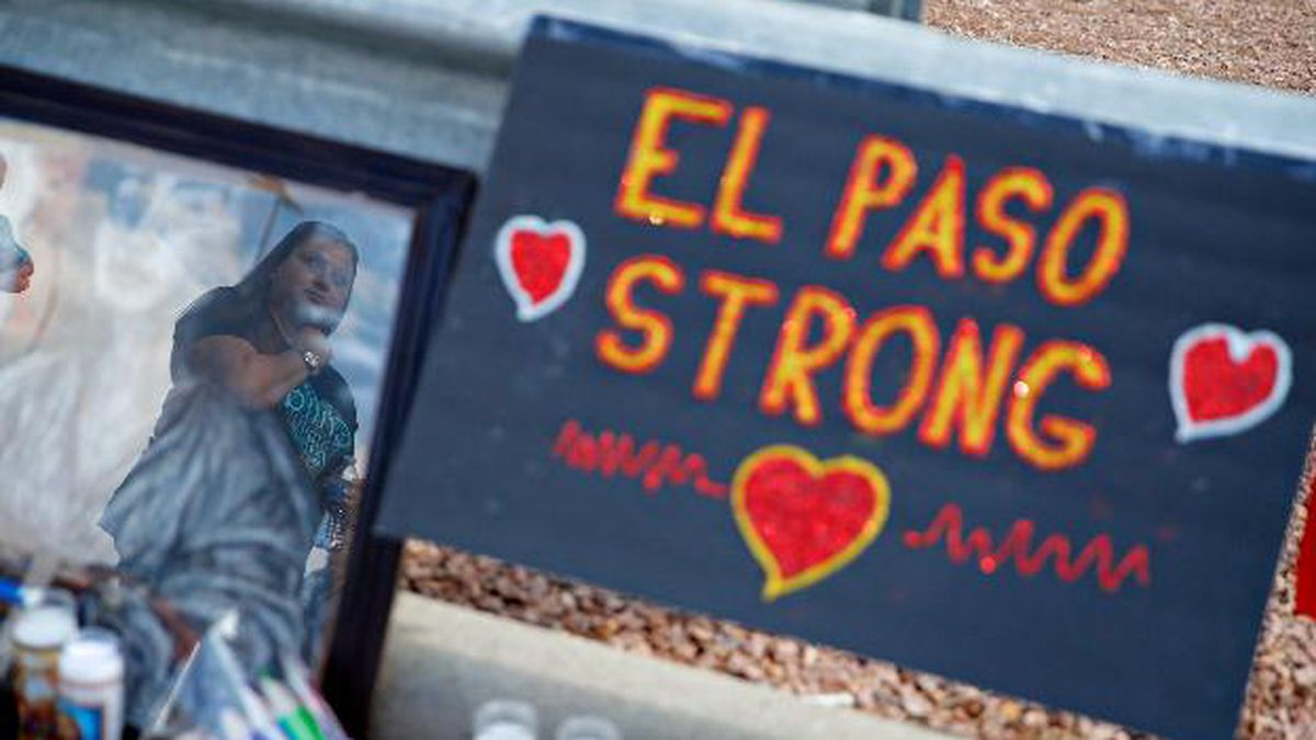 A woman is reflected in a picture as she looks at a makeshift memorial at the scene of a mass shooting at a shopping complex Tuesday, Aug. 6, 2019, in El Paso, Texas. Saturday's mass shooting at the Walmart left multiple people dead and more than two dozen others injured. (AP Photo/John Locher)