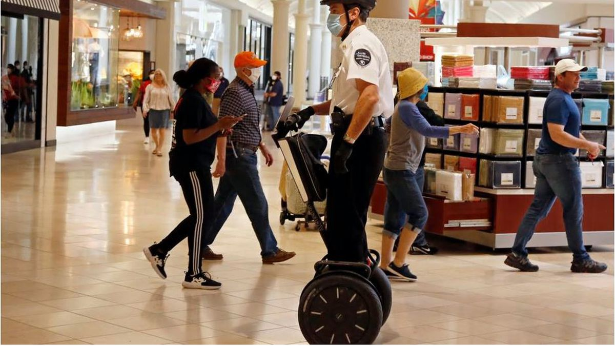 FILE - In this May 1, 2020 file photo, a security guard wearing a mask and riding a Segway...