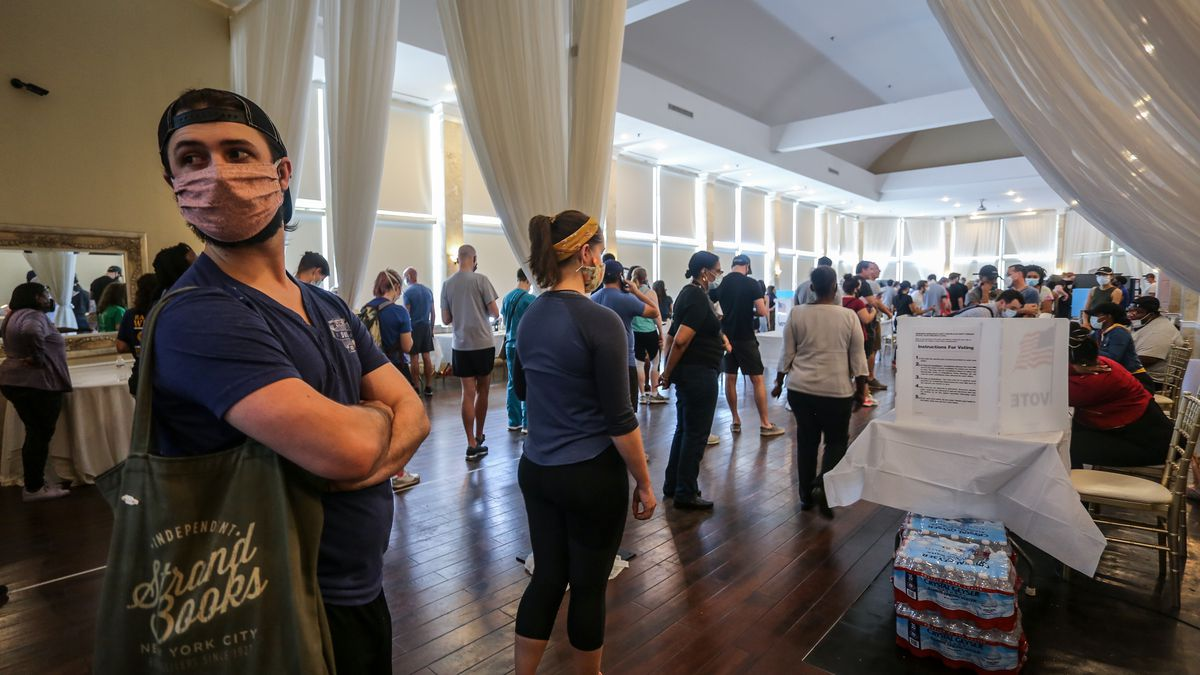 Voters wait in line to cast their ballots in the state's primary election at a polling place, Tuesday, June 9, 2020, in Atlanta, Ga.