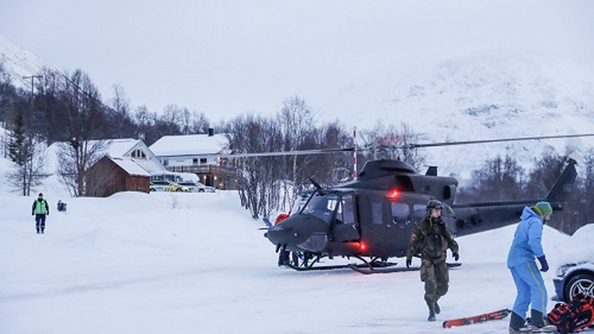 A military helicopter and rescue workers arrive to take part in the search for four missing...