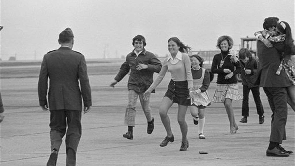 Former POW Capt. Carl D. Chambers, far right, of Yuba City, is greeted by his wife while at left, Lt. Col. Robert Stirm of Foster City meets his family following the servicemen's arrival from the Philippines at Travis AFB, Calif., March 18, 1973. (AP Photo/Sal Veder)