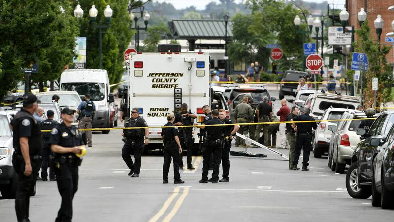 Police officers investigate the scene of an early afternoon shooting in Olde Town Arvada on...