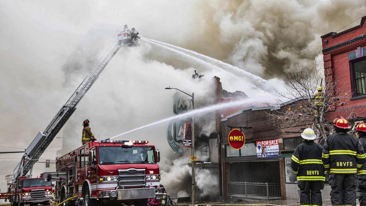 Firefighters battle a flare-up in a fire that destroyed the historic M&M Cigar Shop bar and...