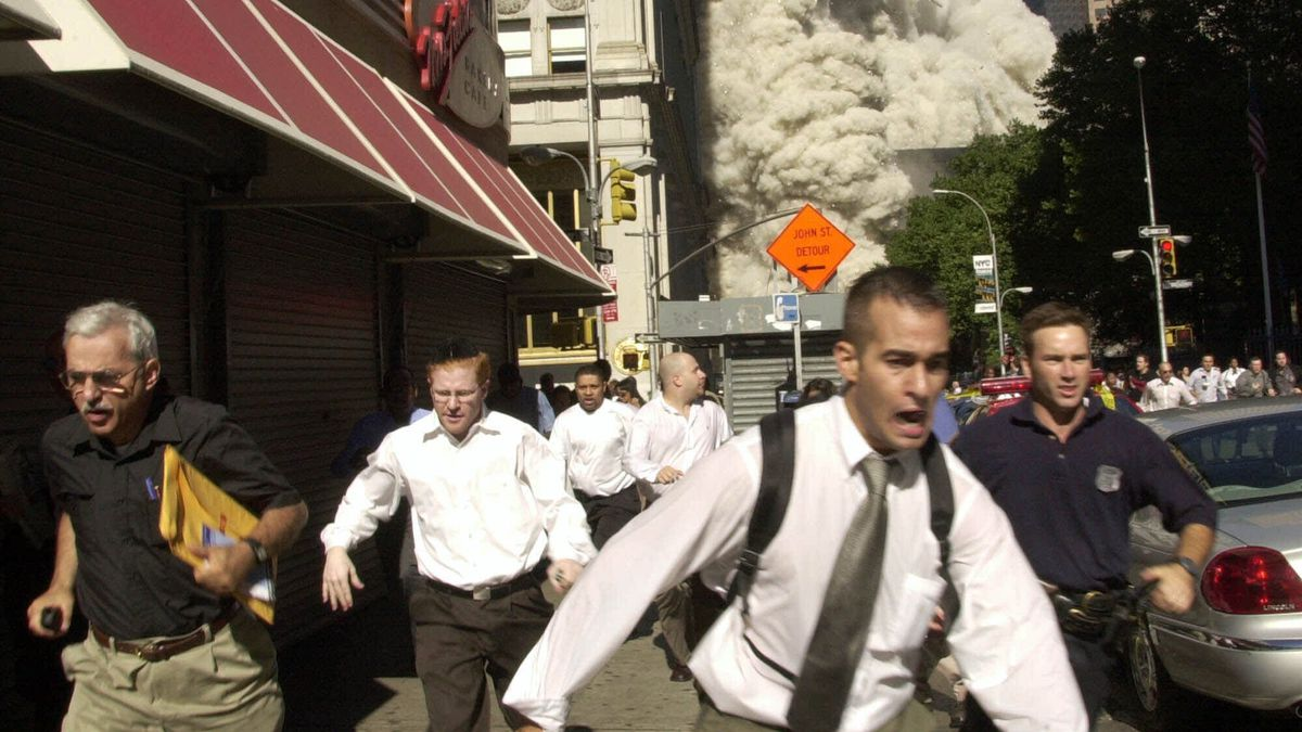 In this Sept. 11, 2001, file photo, people run from the collapse of one of the twin towers at the World Trade Center in New York. Stephen Cooper, far left, fleeing smoke and debris as the south tower crumbled just a block away on Sept. 11, has died from coronavirus, his family said, according to The Palm Beach Post.