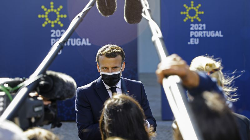 French President Emmanuel Macron speaks with the media as he arrives for an EU summit at the...